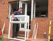 A Window fitter removing old windows in preparation for new ones - 64514832