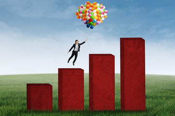 Businesswoman flying with balloons over business graph 1