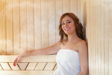 Beautiful young woman relaxing in a sauna.