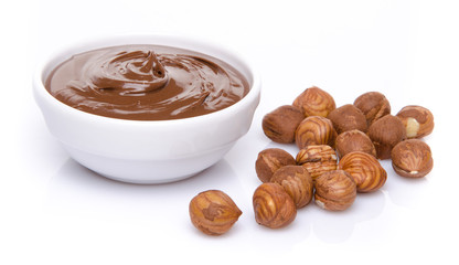 A cup of chocolate hazelnut spread with hazelnuts