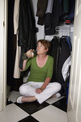 Mature woman drinking from a bottle while hiding in a closet