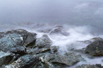 Eddy tide crashing against rocks on shoreline