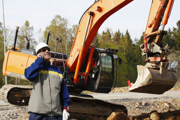 driver and worker with large bulldozer in action