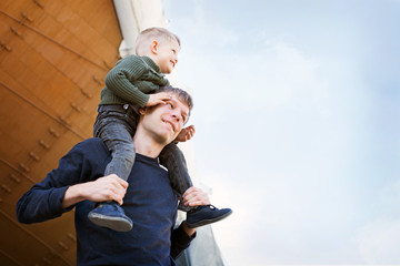 A father and son are looking up at the sky with clouds
