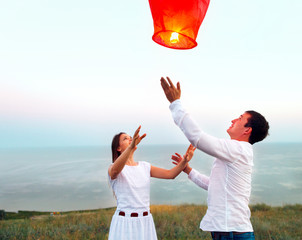 Young couple start a red Chinese sky lantern in the dusk