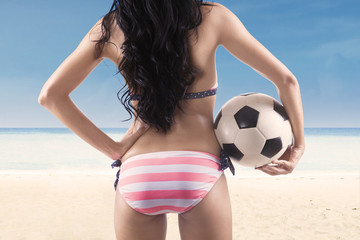 Sexy soccer fan wearing bikini at beach