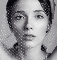 beautiful young woman with dark hair with veil on the face