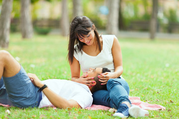 Two people sitting in the park on a picnic and having fun