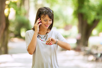 Woman checking the time and talking on the phone outdoors.