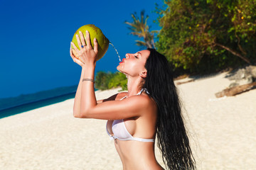 Young beautiful woman with long black hair in white bikini, drin