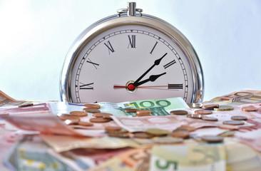 zeit ist geld, Geldscheine und Münzen im Hintergrund eine Uhr