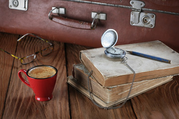 cup of coffee, vintage suitcase, watches, glasses and old books
