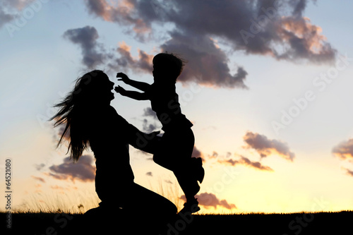 Silhouette of Child Running to Hug Mother at Sunset - 64521080