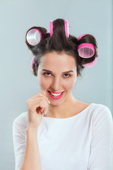 Portrait of a young beautiful housewife with curlers.