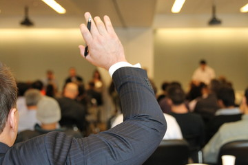 Businessman raising hand during business conference