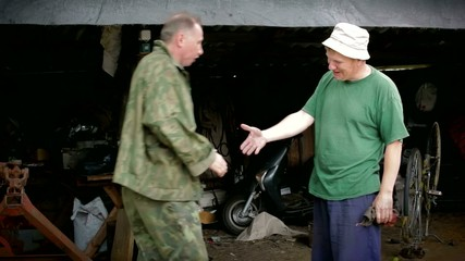Two village mens is meeting in the morning in garage