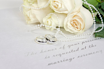 white roses and rings on wedding invitation