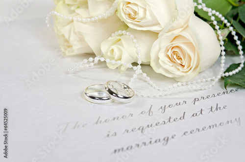 white roses and rings on wedding invitation - 64525009