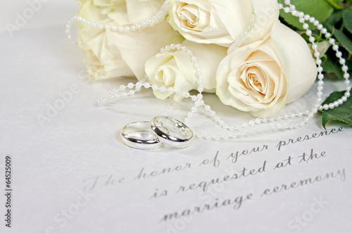 Leinwandbild Motiv white roses and rings on wedding invitation