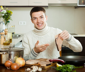 Happy  man holding raw steak of fish