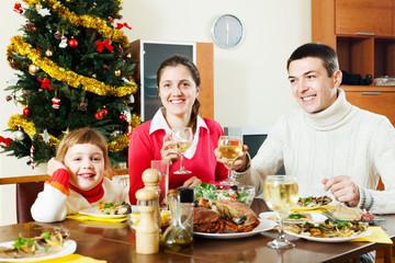 Happy family of three having Christmas dinner