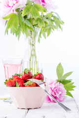 Strawberries in a pink bowl with blooming peony.