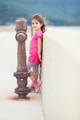Little girl standing on the pier by the sea. Toned image.