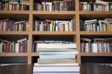 Pila de libros con estantes con libros al fondo