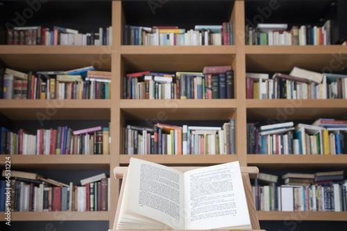 Libro abierto sobre atril con librería de fondo 2