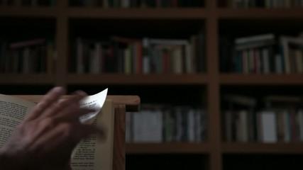 Mano pasando página de libro sobre atril
