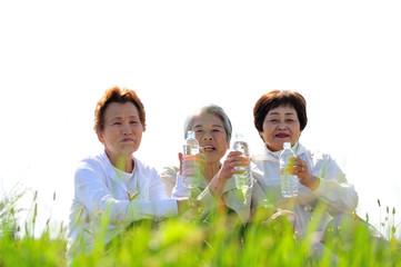 仲良くペットボトルの水を飲んで休憩する3人の高齢者女性