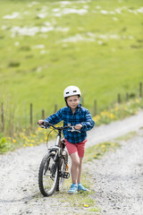 Boy walking uphill with his bike