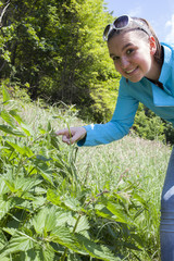 Young smiling woman shows and touch stinging nettle leaves