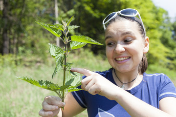 Young cute woman touching stinging nettle leaves