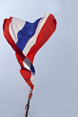 Thai or Thailand nation flag waving gently sway atop on blue sky