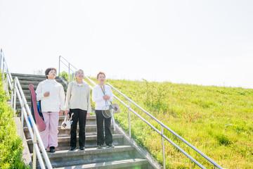 高齢者の3人の女性がスポーツ用具を持って階段を下りている様子