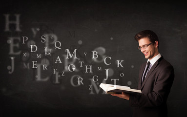 Young man reading a book with alphabet letters