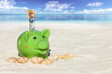 Sparschwein mit Geldscheinen am Sandstrand