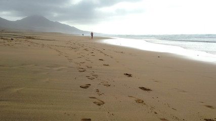 Man jogging on the Cofete beach, Fuerteventura - front view