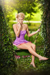 Beautiful young woman in pink short dress dreaming in swing
