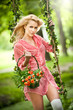 Beautiful young woman in pink dress holding a basket in swing