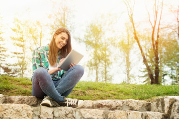 Happy young woman with tablet sitting on stairs in park