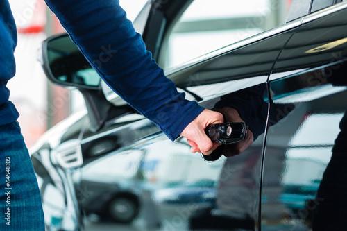 Mann oder Kunde mit Neuwagen von Autohaus - 64541009