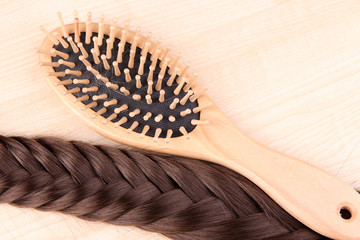 Long brown hair with hairbrush on wooden background