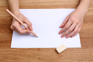 Human hands with pencil writing