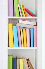 Books on white shelves close-up