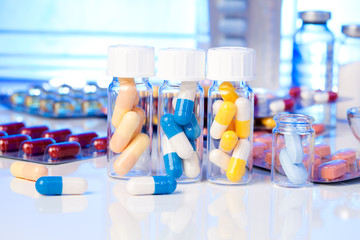 Colorful medical capsules in bottle, on white background.