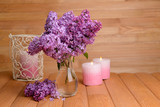 Beautiful lilac flowers in vase on table on wooden background