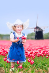 Funny girl in Dutch costume in tulips field with windmill