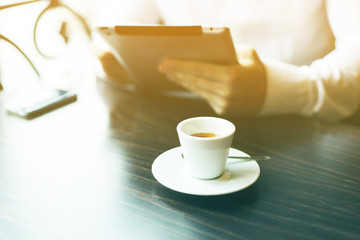 Morning coffe on table. In background man with tablet computer